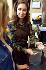 Beautiful young woman customer choosing tea sold by weight in organic shop.
