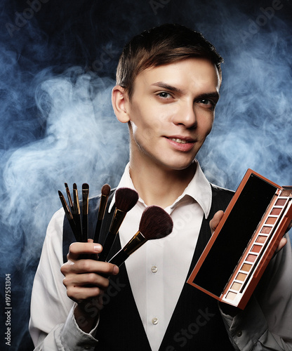 Beauty concept. Young male make up artist posing with make-up brushes and shadow palette on a dark background.