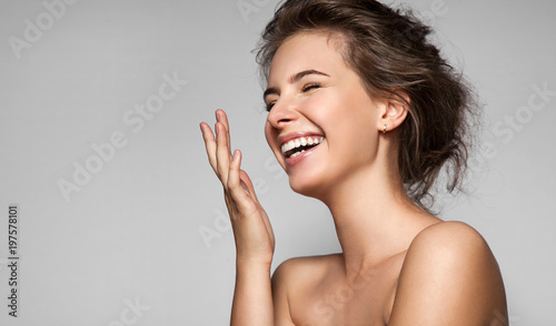 Leinwanddruck Bild A happy laughing young woman with perfect skin, natural make-up and a beautiful smile. Female portrait with bare shoulders on a gray background