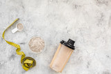 nutrition for workout with protein cocktail, powder and bars on stone background top view mockup