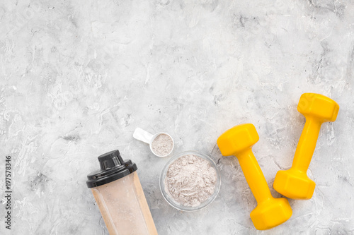 protein powder for fitness nutrition to start training and bars on gray background top view mock-up