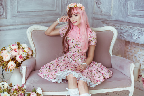 Beautiful young woman doll in a pink dress in a room with flowers, sitting on the couch, lolita. Japanese street fashion.