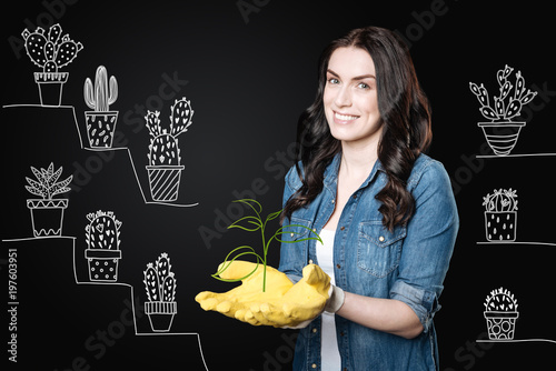 Enthusiastic gardener. Cheerful emotional enthusiastic woman wearing yellow rubber gloves and smiling while working with her beautiful plants in the garden