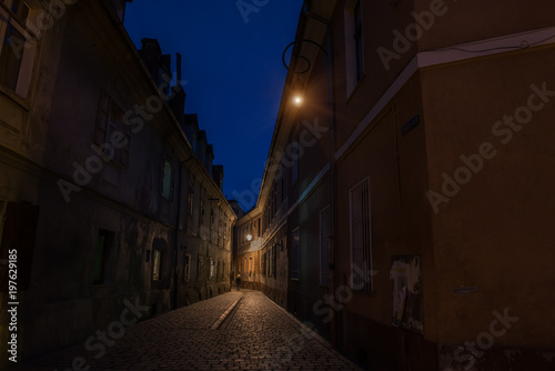 Fotobehang Smalle straatjes Narrow ancient street of the old city. night photo. Brasov. Romania. Europe.