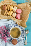 Macaroons and coffee. Blue, rose and baige colors. Wooden table. Macaroons in the box, coffee in white porcelain cup.