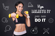 Strong person. Positive young active woman feeling strong and confident while being in a modern gym and doing exercises with yellow hand weights