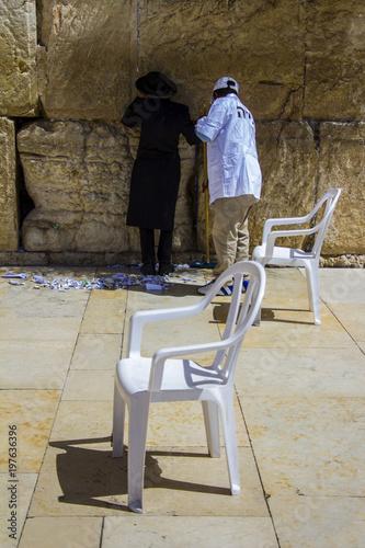 Aluminium Reznik Религиозный ортодоксальный еврей молится у стены, а дворник приближается. Иерусалим, Израиль.