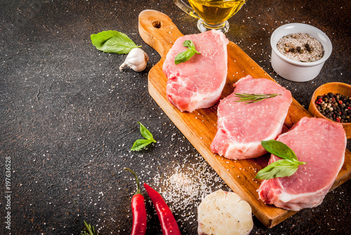 Foto op Plexiglas Steakhouse Raw meat, pork steaks with spices, herbs, olive oil, dark background copy space