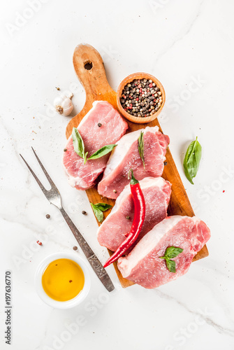 Raw meat, pork steaks with spices, herbs, olive oil, white marble background on cutting board, top view, copy space - 197636770