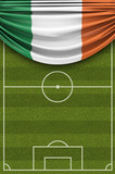 Ireland country flag draped over a football soccer pitch. 3D Rendering