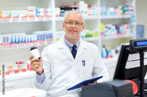 Fotobehang Apotheek medicine, healthcare and people concept - senior apothecary with drug at pharmacy cash register