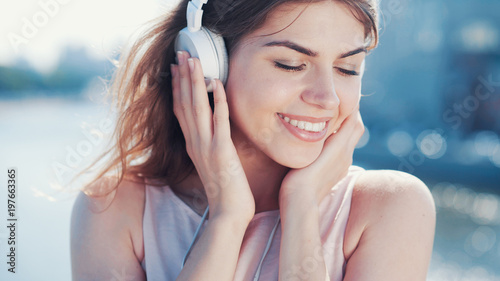 Smiling girl listen to music outdoors - 197663365