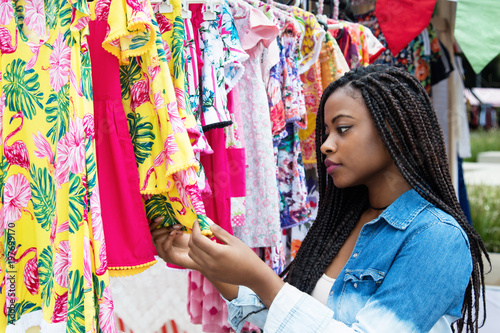 African american woman shopping colorful clothes at market