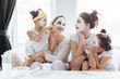 Mom with her daughters making clay face mask. Mother with children doing beauty treatment together. Morning skin care routine.