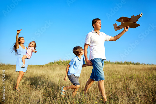 Happy family playing walks on nature in the summer.
