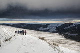 Several hikers in stormy winter landscape in Brecon Beacons