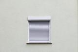 geschlossenes Fenster mit Rollo an einer weißen Wand