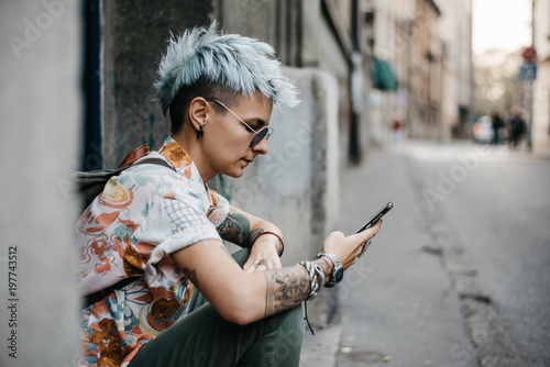 Urban stylish woman with blue hair sitting on the street and using her phone