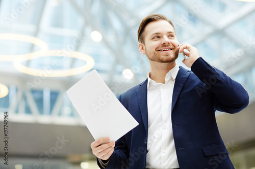 Smiling agent with paper and smartphone consulting one of his client about contract terms