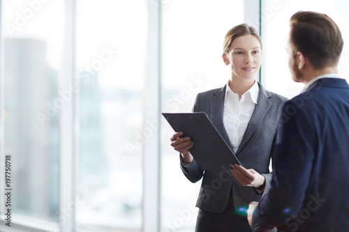 Young elegant employees discussing document or contract and its points at meeting in office