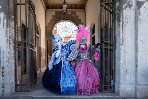 Two women in masks and ornate blue and pink costumes standing near the Rialto Market at Venice Carnival (Carnivale di Venezia)
