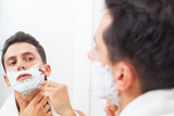 Guy shaving his beard with razor at the bathroom