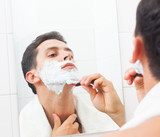 Handsome man shaving his beard with razor at the bathroom
