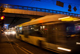 The motion of a blurred trolleybus on the street at dusk under the bridge
