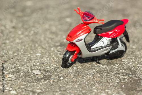 Foto op Canvas Scooter little toy red motorbyke on a ground with space for copy or text