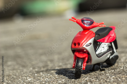 Fotobehang Scooter little toy red motorbyke on a ground with space for copy or text