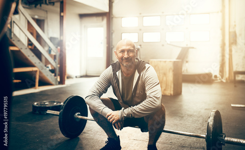 Smiling mature man crouching by weights in a gym