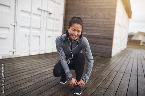 Young Asian woman tying her running shoes before a run