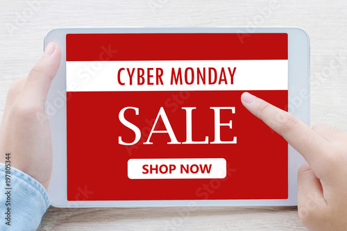 Hand using tablet with cyber monday sale on screen device over blur background with copy space, business technology and lifestyle concept