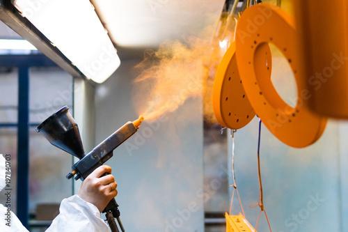 Lakierowanie proszkowe części metalowych. Kobieta w stroju ochronnym rozpyla farbę proszkową z pistoletu na wyroby metalowe