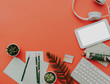 Flat lay trendy workspace with keyboard, diary, succulent and accessories on orange background. Top view