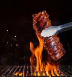 Pork ribs over flaming grill grid, isolated on black background.