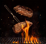 Flying beef steaks over grill grid, isolated on black background - 197853341