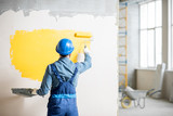 Workman in uniform painting wall with yellow paint at the construction site indoors - 197858567