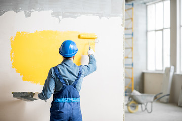 Workman in uniform painting wall with yellow paint at the construction site indoors