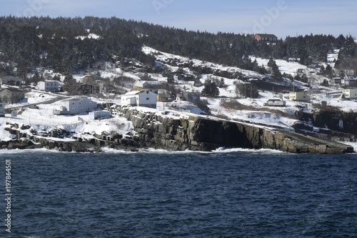 view across the bay towards the fishing village of Flatrock Newfoundland, Canada, landscape with ocean and forest during Winter
