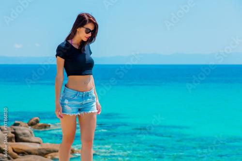 Foto Murales Young beautiful girl on a rock near a sea coast in Greece