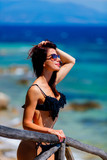 Young beautiful girl in bikini on the beach in Greece. Summertime vacation concept
