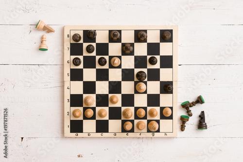 Odgórny widok na drewnianej szachowej desce z postaciami podczas gry na białym drewnianym stołowym tle