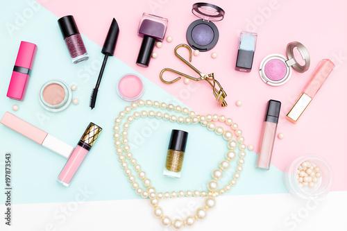 Kosmetyki dekoracyjne i perły na różowym tle. płaskie lay