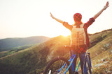 Woman tourist on a bicycle at top of mountain at sunset outdoors during a hike in summer