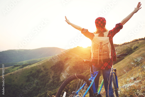 Woman tourist on a bicycle at top of mountain at sunset outdoors during a hike in summer - 197882530