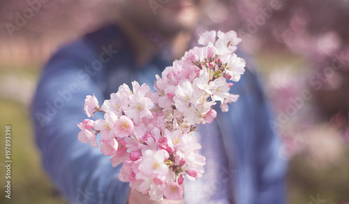 a young man giving boquet of pink flowers, spring, love and romantic concept. Horizontal