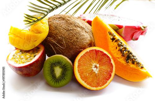 Foto Murales fresh tropical fruits - rambutan, papaya, kiwi, mango on a wooden background