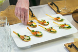 Delicates, appetizer filling with red fish, quail egg, black caviar and lime. Catering service during table decoration.