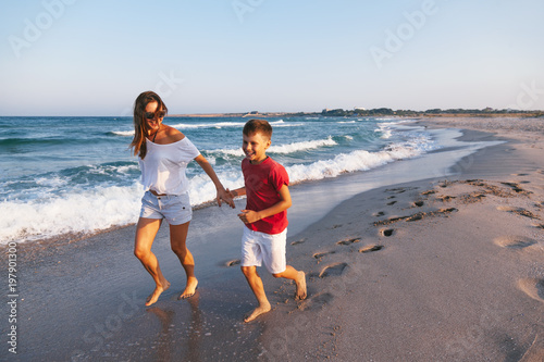 Mom and son walking and playing on the beach